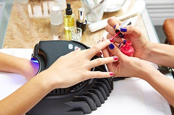Painting nails on one hand while the other hand is drying under a a UV light