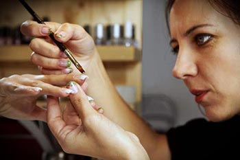Manicurist aplying gel nail polish to a young womans nails