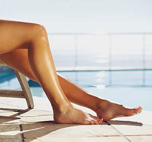 Tanned and waxed legs by the pool