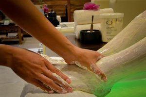 Pedicurist applying a sugar scrub to a young womans feet